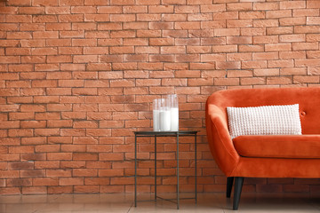 Comfortable sofa and table near brick wall