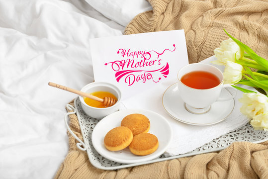 """Card with text """"Happy Mother's day"""" and tasty breakfast on bed"""
