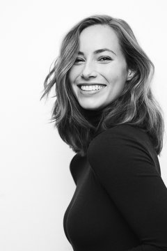 Black and white portrait of a young happy woman with a big smile on her face