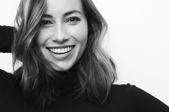 Black and white portrait of young happy woman with a big smile on her face looking in camera