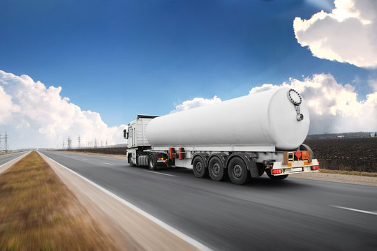 Big fuel tanker truck shipping fuel on the countryside road in motion against sky