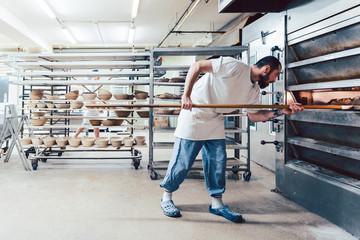 Baker checking bread in the baker oven