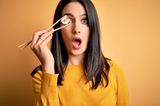 Young brunette woman with blue eyes eating salmon maki sushi using chopsticks scared in shock with a surprise face, afraid and excited with fear expression