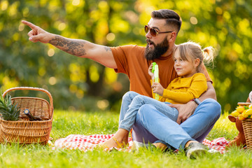 Joyful family picnicking in summer park