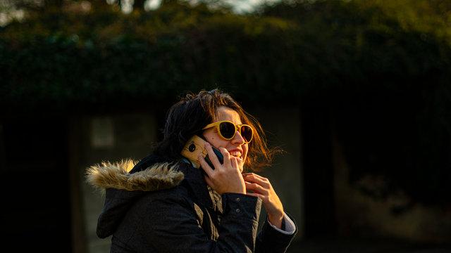 mujer, celular, llamada telefónica, risa, anteojos de sol, cielo, parque, modelo, soleado, contraluz