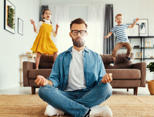 Father meditating in room with playful kids