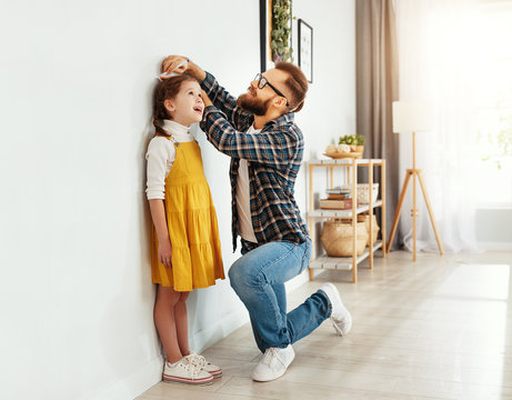 father measuring height of daughter at home.