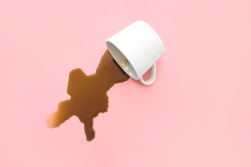 Overturned cup of coffee on color background