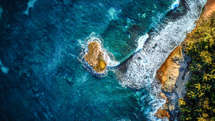Printed roller blinds Island Aerial drone photo of a tiny island in a turquoise transparent water of an ocean, surrounded by sandy beach and palm trees of a tropical resort. View from the top