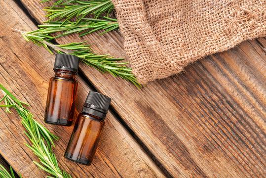 Bottles of rosemary essential oil on table