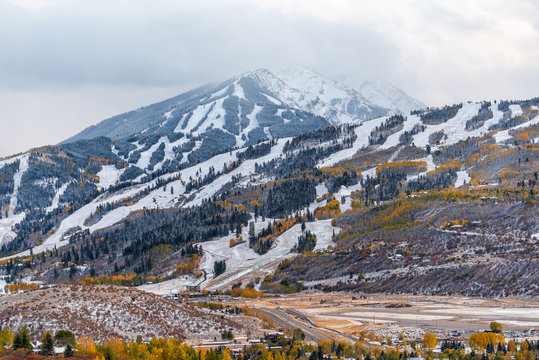 Aspen, Colorado USA city with buttermilk ski slope in rocky mountains view of storm clouds and small airport runway in roaring fork valley