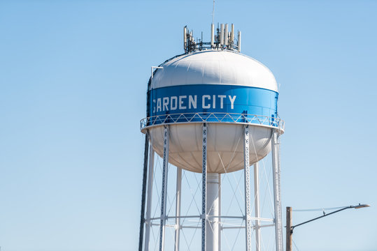 View of water tower sign for Garden City in Kansas countryside industrial town closeup isolated against sky