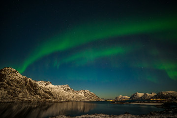 Photo sur Toile Aurore polaire Aurora borealis on the Lofoten islands, Norway. Green northern lights above mountains. Night sky with polar lights. Night winter landscape with aurora and reflection on the water surface