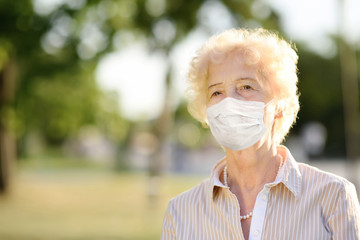 Outdoors portrait senior woman wearing disposable medical face mask. Safety in public place during coronavirus outbreak.