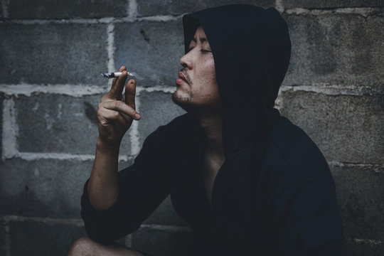 A man smokes cannabis weed, a joint and a lighter in his hands. Concepts of medical marijuana use and legalization of the cannabis.