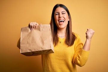 Young beautiful woman holding take away paper bag from delivery over yellow background screaming...