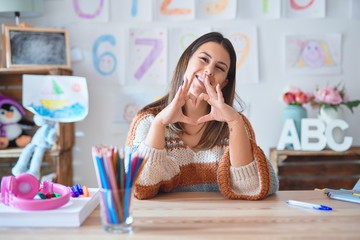 Young beautiful teacher woman wearing sweater and glasses sitting on desk at kindergarten smiling...