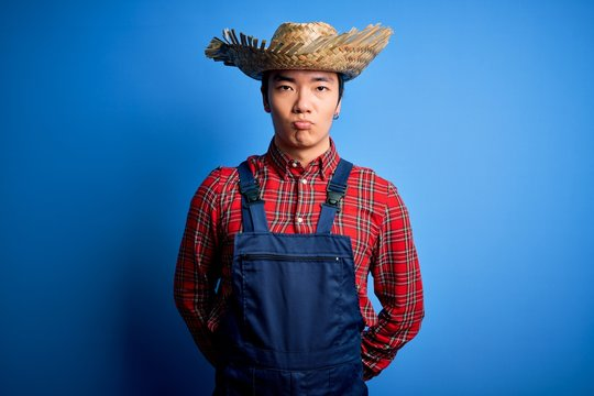 Young handsome chinese farmer man wearing apron and straw hat over blue background depressed and worry for distress, crying angry and afraid. Sad expression.