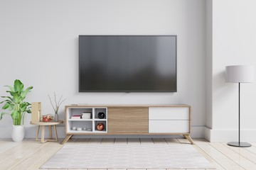 TV on the cabinet in modern living room with plant on white wall background.