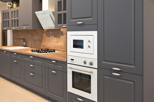 Interior of modern kitchen equipment and grey cabinets