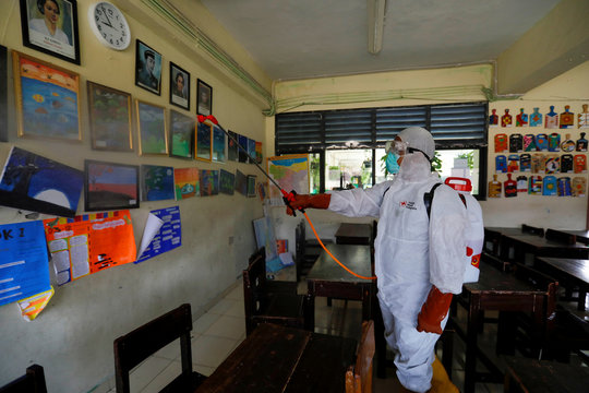 A volunteer from Indonesia's Red Cross sprays disinfectant inside the classroom of a school closed amid the spread of coronavirus in Jakarta