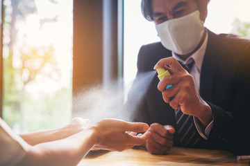 Businessman with mask applying alcohol spray for cleaning and protecting colleague hands from virus disease
