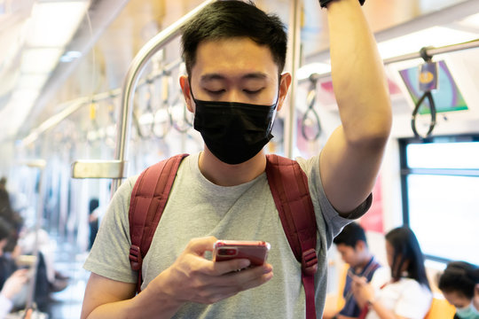 Close up of one young Asian man wearing black surgical face mask and using mobile phone in subway train during Coronavirus Covid-19 pneumonia outbreak and pm 2.5 smog air pollution crisis in big city.
