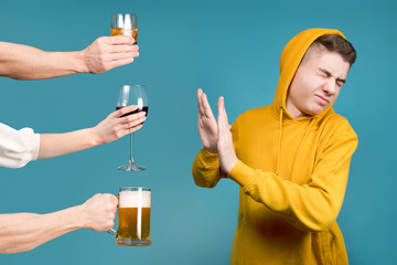 Teenager in a yellow sweatshirt refuses different types of alcohol