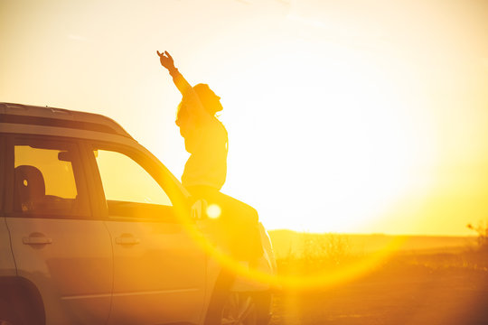 woman stop at roadside to enjoy sunset. sitting on car hood