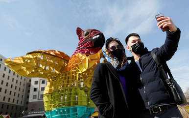 People wearing protective face masks take pictures with the installation of a squirrel in Almaty
