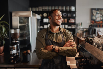Young afro-american small coffee shop owner standing behind counter wearing apron with crossed arms looking away