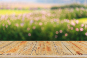 Empty wood table top and blurred green tree and flower in agricultural organic farm background - can used for display or montage your products.
