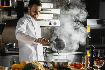 caucasian cook enjoy the process of cooking in the kitchen. man love his job in restaurant. chef in white uniform steaming, frying food