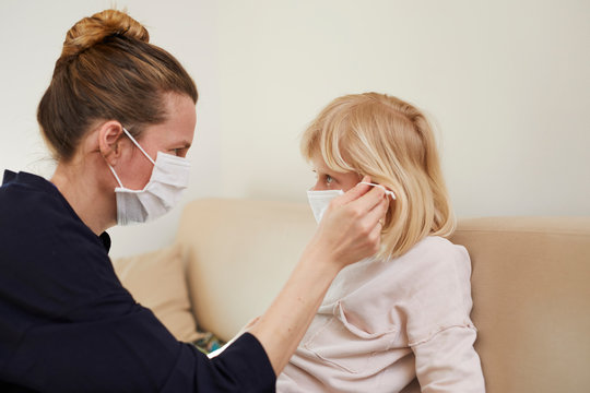 Mutter mit Kind tragen Maske zuhause
