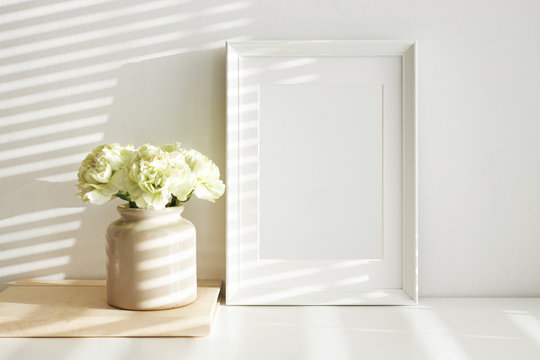 Horizontal shot of blank white photo frame for family picture and stylish ceramic vase with beautiful peony flowers, morning sunshine on wall. Interior design, coziness and decoration concept