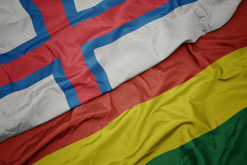 Deurstickers Noord Europa waving colorful flag of bolivia and national flag of faroe islands.