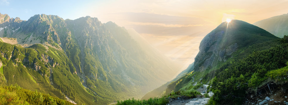 Deep mountain valley in morning sunlight, panoramic view