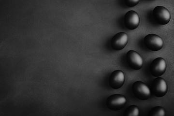 Black eggs on a black background. Easter minimalistic concept