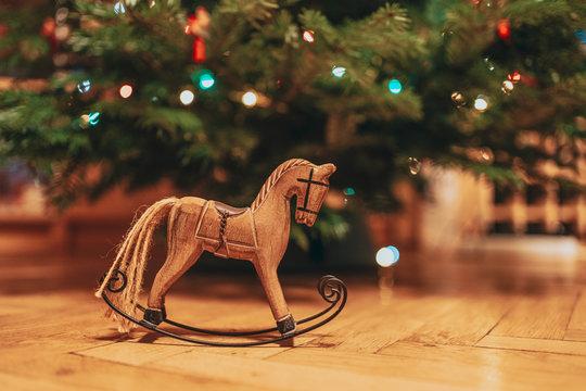 Wood horse Christmas decorative underneath a Christmas tree