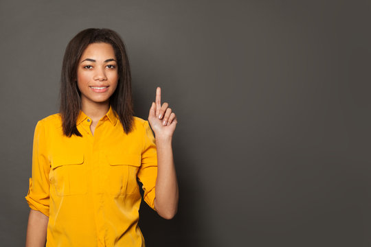 Happy African American woman pointing up on gray banner background