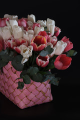 Tuinposter Lelie White and pink tulips in a pink wicker basket on a black background.