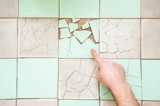 Man finger pointing to cracked old tiles on floor. Closeup. Top down view.
