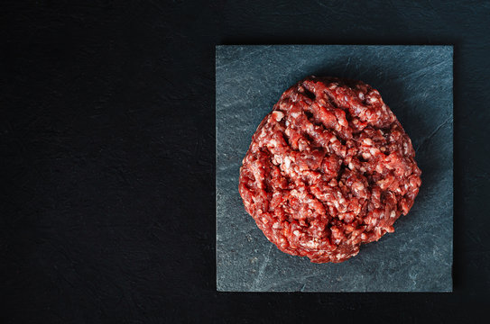 pile of fresh raw minced meat for cutlets on a black background.
