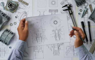 Engineer technician designing drawings mechanical parts engineering Engine.manufacturing factory Industry Industrial work project blueprints measuring bearings caliper tools