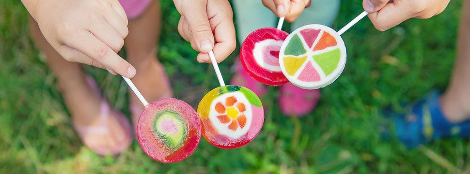 Lollipops in the hands of children. Selective focus.