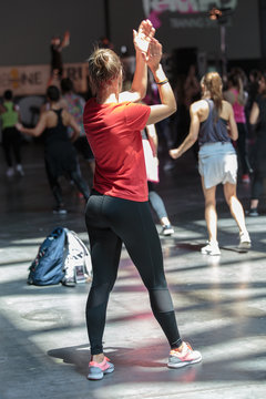 Fitness Workout in Gym: People doing Exercises in Class with Music and Teacher on Stage