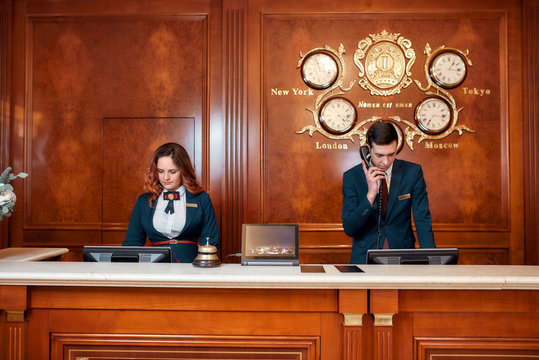 Working process. Attractive executives at the reception desk of a hotel. Young man answering phone call