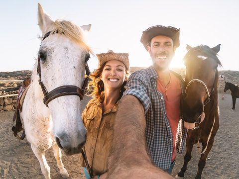 Happy couple taking selfie with horses inside stable - Young farmers having fun with animals in corral ranch - Human and animals relationship lifestyle concept