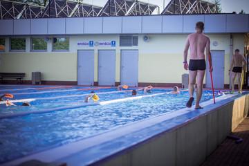 Fototapeta Summer camp, Trener uczy pływać dzieci na basenie pływalni obraz