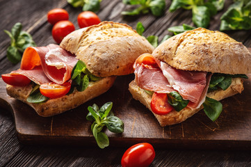 Obraz Jamon sandwiches with tomatoes, on wooden board. - fototapety do salonu